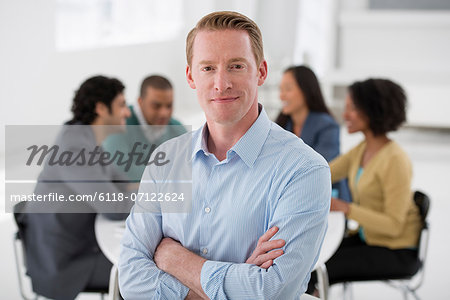 Business Meeting. A Group Sitting Down Around A Table. A Man Smiling Confidently.