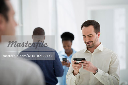 Office Interior. A Group Of People, One Man Using A Smart Phone. Stock Photo - Premium Royalty-Free, Image code: 6118-07122639