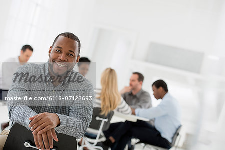 Office Interior. A Man Seated Separately From A Group Of People Seated Around A Table. A Business Meeting. Stock Photo - Premium Royalty-Free, Image code: 6118-07122693