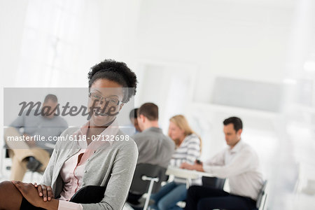 Office Interior. A Group Of People Meeting. One Person Looking Over Her Shoulder And Away From The Group. Stock Photo - Premium Royalty-Free, Image code: 6118-07122698