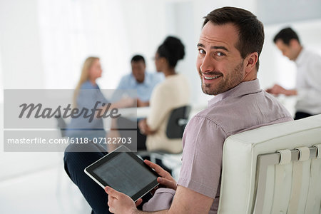 Office Interior. Meeting. One Person Looking Over His Shoulder And Away From The Group. Holding A Digital Tablet. Stock Photo - Premium Royalty-Free, Image code: 6118-07122703
