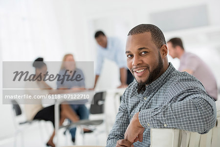 Office Interior. Meeting. One Person Looking Over Her Shoulder And Away From The Group. Stock Photo - Premium Royalty-Free, Image code: 6118-07122710