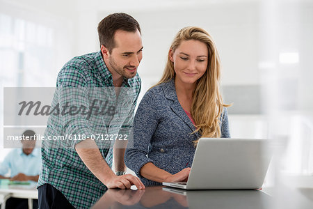 Office Interior. A Couple At A Table Looking At A Computer Screen. Stock Photo - Premium Royalty-Free, Image code: 6118-07122722