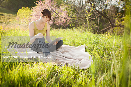 A Young Woman Sitting In A Field, On A Blanket, Reading From A Digital Tablet. Stock Photo - Premium Royalty-Free, Image code: 6118-07122740