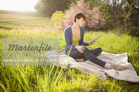 A Young Woman Sitting In A Field, On A Blanket, Holding And Looking At The Screen Of A Digital Tablet. Working Outdoors. Stock Photo - Premium Royalty-Free, Image code: 6118-07122741