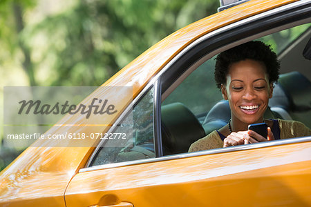 A Woman Sitting In The Rear Passenger Seat Of A Yellow Cab, Checking Her Phone. Stock Photo - Premium Royalty-Free, Image code: 6118-07122772