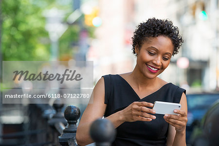 People On The Move. A Woman In A Black Dress On A City Street, Checking Her Phone. Stock Photo - Premium Royalty-Free, Image code: 6118-07122780