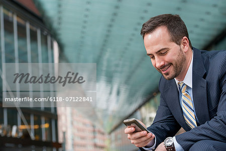City. A Man In A Business Suit Checking His Messages On His Smart Phone. Stock Photo - Premium Royalty-Free, Image code: 6118-07122841