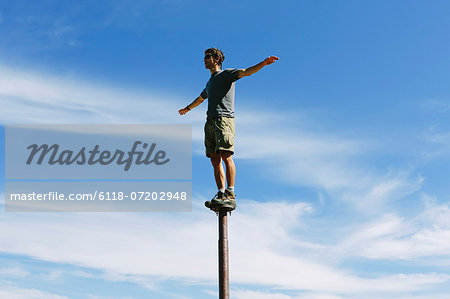 Man standing and balancing on a metal post, looking towards expansive sky, on Surprise Mountain, Alpine Lakes Wilderness, Mt. Baker-Snoqualmie National forest. Stock Photo - Premium Royalty-Free, Image code: 6118-07202948