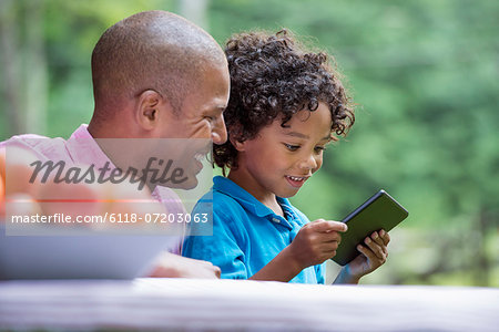 A picnic on the farm. Fresh organic fruit on the table. A father and son sitting together. Stock Photo - Premium Royalty-Free, Image code: 6118-07203063