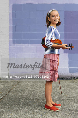 A ten year old girl holding a violin under her arm and a bow in her hand. Stock Photo - Premium Royalty-Free, Image code: 6118-07203262