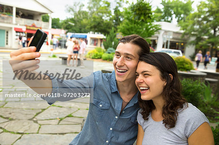 A young couple side by side, flirting and taking photographs. Stock Photo - Premium Royalty-Free, Image code: 6118-07203272