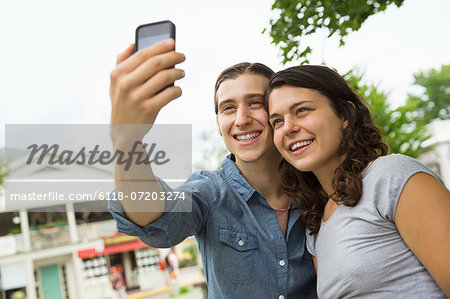 A young couple side by side, flirting and taking photographs. Stock Photo - Premium Royalty-Free, Image code: 6118-07203274