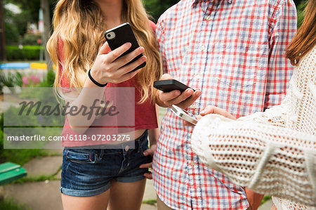 Two friends, a boy and girl looking at their phones. Stock Photo - Premium Royalty-Free, Image code: 6118-07203275