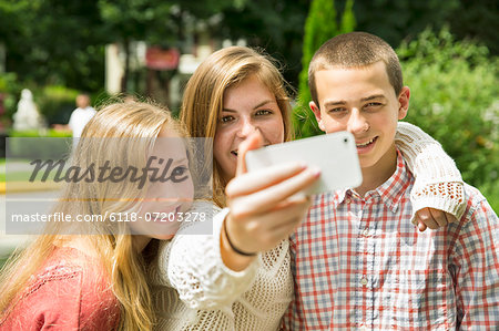 Three young people, two girls and a boy, posing and taking selfy photographs. Stock Photo - Premium Royalty-Free, Image code: 6118-07203278