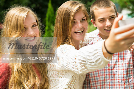 Three young people, two girls and a boy, posing and taking selfy photographs. Stock Photo - Premium Royalty-Free, Image code: 6118-07203279