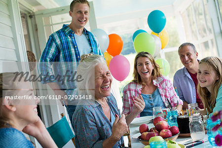 A birthday party in a farmhouse kitchen. A group of adults and children gathered around a chocolate cake. Stock Photo - Premium Royalty-Free, Image code: 6118-07203418