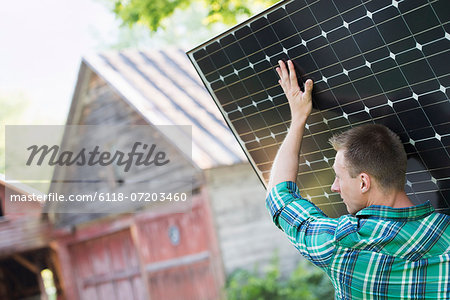 A man carrying a solar panel towards a building under construction. Stock Photo - Premium Royalty-Free, Image code: 6118-07203460