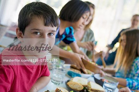 A family party around a table in a cafe. Adults and children. Stock Photo - Premium Royalty-Free, Image code: 6118-07203585