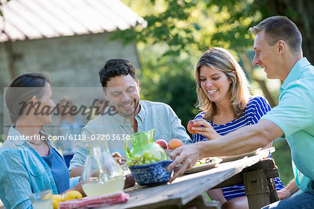 A family, adults and children seated around a table, enjoying a meal together. Stock Photo - Premium Royalty-Free, Image code: 6118-07203630