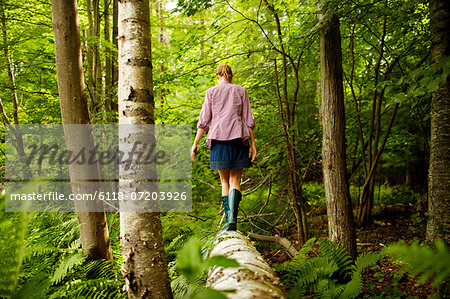 A woman in wellingtons walking along a fallen tree trunk, in woodland. Stock Photo - Premium Royalty-Free, Image code: 6118-07203926