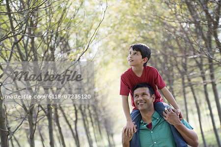 A boy having a piggyback, riding on a man's shoulders. Stock Photo - Premium Royalty-Free, Image code: 6118-07235120