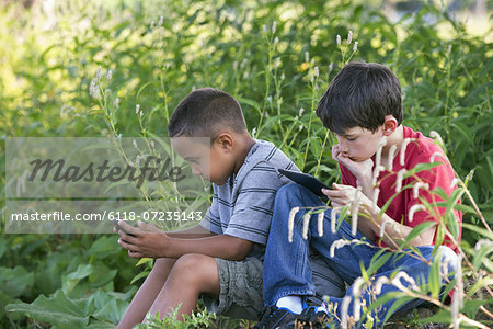 Two boys sitting in a field, one on a smart phone and one using a digital tablet. Stock Photo - Premium Royalty-Free, Image code: 6118-07235143
