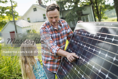 A man and a young girl looking at a solar panel in a garden. Stock Photo - Premium Royalty-Free, Image code: 6118-07235254