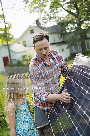 A man and a young girl looking at a solar panel in a garden. Stock Photo - Premium Royalty-Free, Image code: 6118-07235255