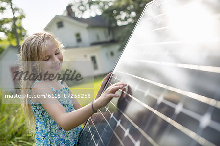 A young girl beside a large solar panel in a farmhouse garden. Stock Photo - Premium Royalty-Free, Image code: 6118-07235256