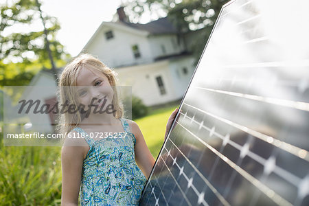 A young girl beside a large solar panel in a farmhouse garden. Stock Photo - Premium Royalty-Free, Image code: 6118-07235257