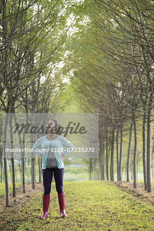 A woman between two rows of trees, looking upwards. Stock Photo - Premium Royalty-Free, Image code: 6118-07235272