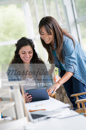 Two women working together, looking at the screen of a digital tablet. Stock Photo - Premium Royalty-Free, Image code: 6118-07351178