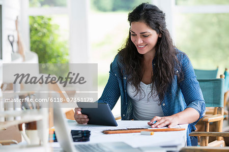 A woman working at a table, using a digital tablet. Stock Photo - Premium Royalty-Free, Image code: 6118-07351179