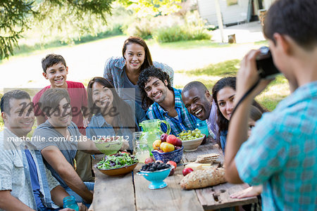 A summer party outdoors. Adults and children posing for a photograph. Stock Photo - Premium Royalty-Free, Image code: 6118-07351212