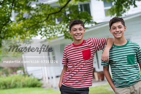 Two boys in a farmhouse garden in summer. Stock Photo - Premium Royalty-Free, Image code: 6118-07351226