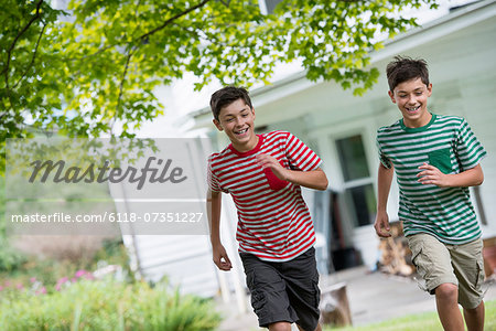 Two boys in a farmhouse garden in summer. Stock Photo - Premium Royalty-Free, Image code: 6118-07351227