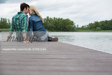 A man and woman seated on a jetty by a lake. Stock Photo - Premium Royalty-Free, Image code: 6118-07351266