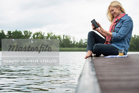 A woman sitting on a jetty by a lake, using a digital tablet. Stock Photo - Premium Royalty-Free, Image code: 6118-07351272