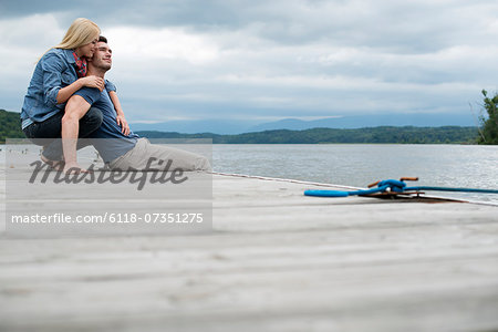 A man and woman seated on a jetty by a lake. Stock Photo - Premium Royalty-Free, Image code: 6118-07351275