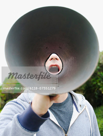 A man using a megaphone in the open air. Stock Photo - Premium Royalty-Free, Image code: 6118-07351279