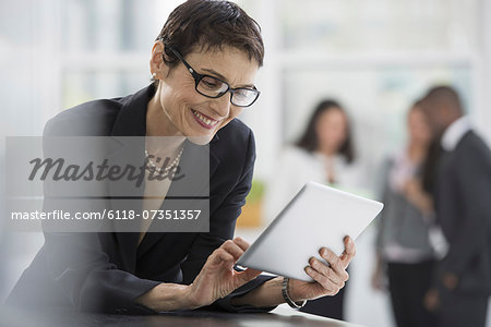 An office interior. A woman in a black jacket using a digital tablet. Stock Photo - Premium Royalty-Free, Image code: 6118-07351357