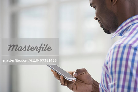 Professionals in the office. A light and airy place of work. A man in a checked shirt using a smart phone. Stock Photo - Premium Royalty-Free, Image code: 6118-07351466