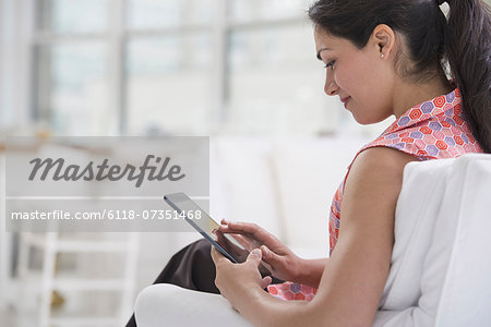 Professionals in the office. A light and airy place of work. A woman seated using a digital tablet. Stock Photo - Premium Royalty-Free, Image code: 6118-07351468