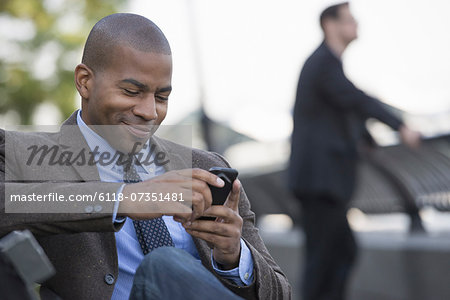Business people in the city. Keeping in touch on the move. A man seated using his smart phone. A man in the background. Stock Photo - Premium Royalty-Free, Image code: 6118-07351481