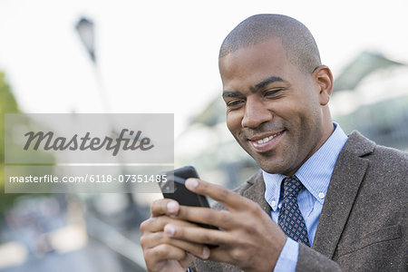 Business people in the city. Keeping in touch on the move. A man using a smart phone. Stock Photo - Premium Royalty-Free, Image code: 6118-07351485