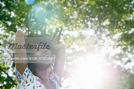A young woman in a flowered summer dress with her hands behind her head, smiling and looking up. Stock Photo - Premium Royalty-Free, Image code: 6118-07351593