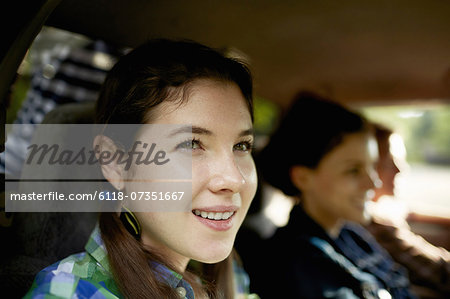 Three passengers in the cab of a pickup truck. One young man driving. Two young women sitting beside him. Stock Photo - Premium Royalty-Free, Image code: 6118-07351667