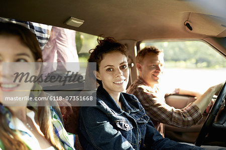 Three passengers in the cab of a pickup truck. One young man driving. Two young women sitting beside him. Stock Photo - Premium Royalty-Free, Image code: 6118-07351668