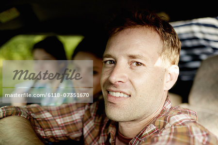 Three passengers in the cab of a pickup truck. One young man driving. Two young women sitting beside him. Stock Photo - Premium Royalty-Free, Image code: 6118-07351670